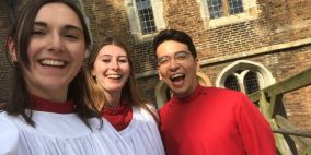 Photo of three Queens' Choristers smiling on Mathematical Bridge