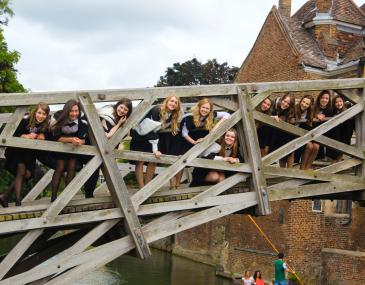 A photograph of graduating students on the Mathematical Bridge, Queens' College.